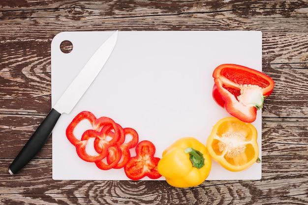 Fette di peperoni rossi con un coltello affilato sul bordo bianco sopra il ripiano del tavolo in legno Foto Gratuite