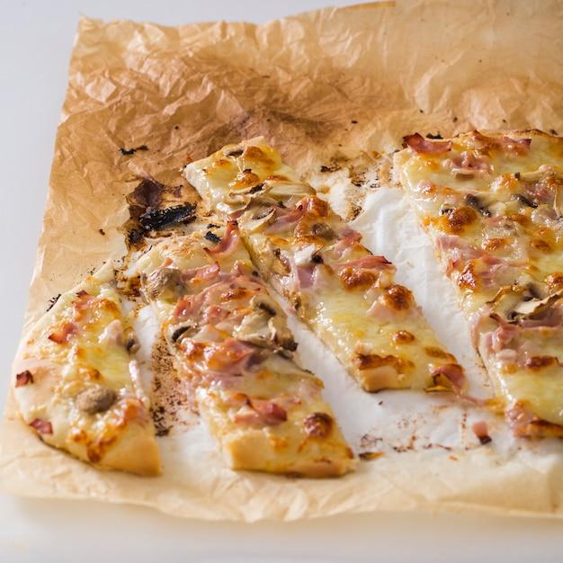 Fette di pizza su carta pergamena contro sfondo bianco Foto Gratuite