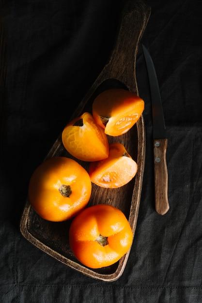 Fette di pomodori arancio su un tagliere e coltello Foto Gratuite