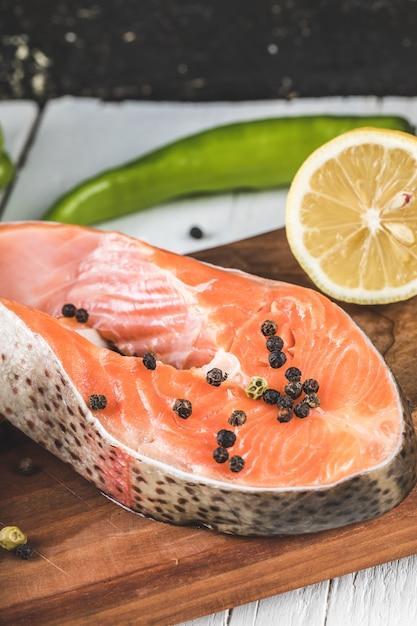 Fette di salmone con palline di pepe nero e limone su una tavola di legno Foto Gratuite