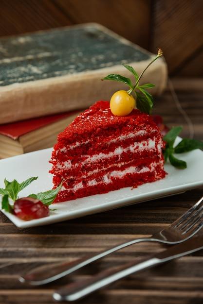 Fette di torta di velluto rosso con ciliegia yellof nella parte superiore e foglie di menta Foto Gratuite