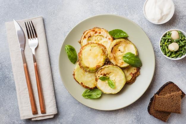 Fette di zucchine fritte in pastella con aglio e basilico su un piatto. Foto Premium