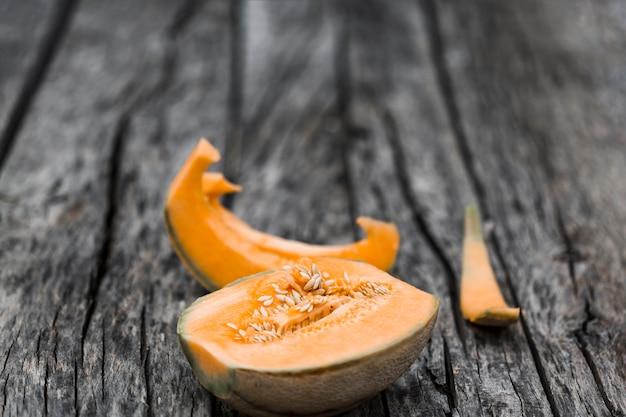 Fette e melone del cantalupo diviso a metà su una vecchia tavola esposta all'aria Foto Gratuite