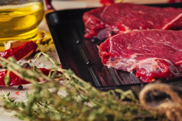 Fette fresche della carne cruda sulla vista superiore della padella. bistecche di manzo pronte per la cottura con olio d'oliva Foto Premium