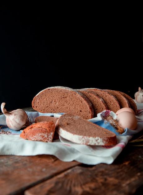 Fette sottili di vista laterale del pane nero tradizionale con farina bianca su di esso, su un asciugamano rustico con aglio e uova, su un tavolo da cucina in legno. Foto Gratuite