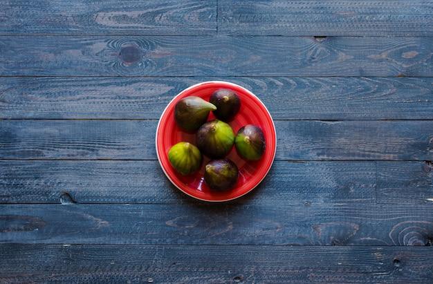 Fichi freschi con pesche, albicocche, mirtilli, fragole, su un tavolo di legno Foto Premium