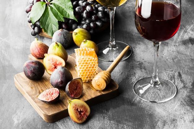 Fico, uva, pane, miele e vino rosso e bianco Foto Premium