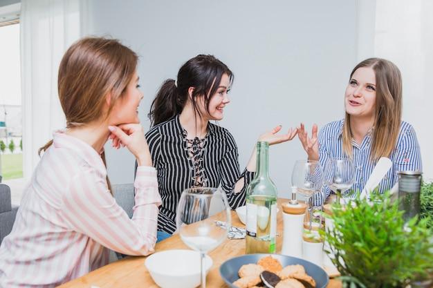 Fidanzate che si siedono al tavolo e in chat Foto Gratuite