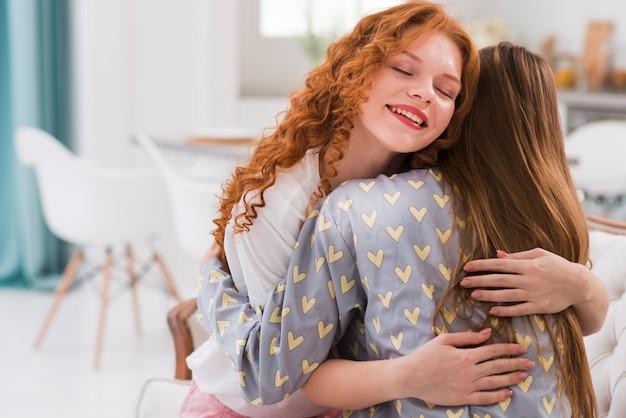 Fidanzate di smiley a casa che abbraccia Foto Gratuite
