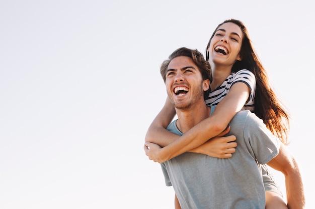 Fidanzato ridendo che trasporta fidanzata ridente in spiaggia Foto Gratuite