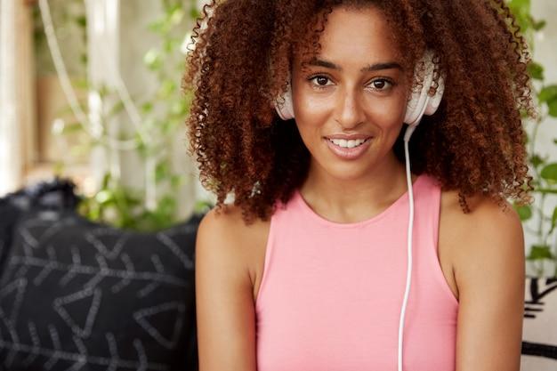Fiduciosa donna afroamericana attraente dalla pelle scura in maglietta rosa casual, ascolta canzoni online in cuffia, gode della composizione preferita, ha riposo a casa. persone, tecnologia, stile di vita Foto Gratuite