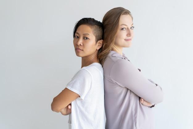 Fiduciose ragazze in piedi schiena contro schiena con le braccia incrociate Foto Gratuite