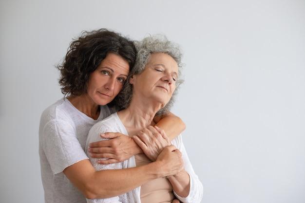 Figlia adulta pensierosa che abbraccia madre senior Foto Gratuite