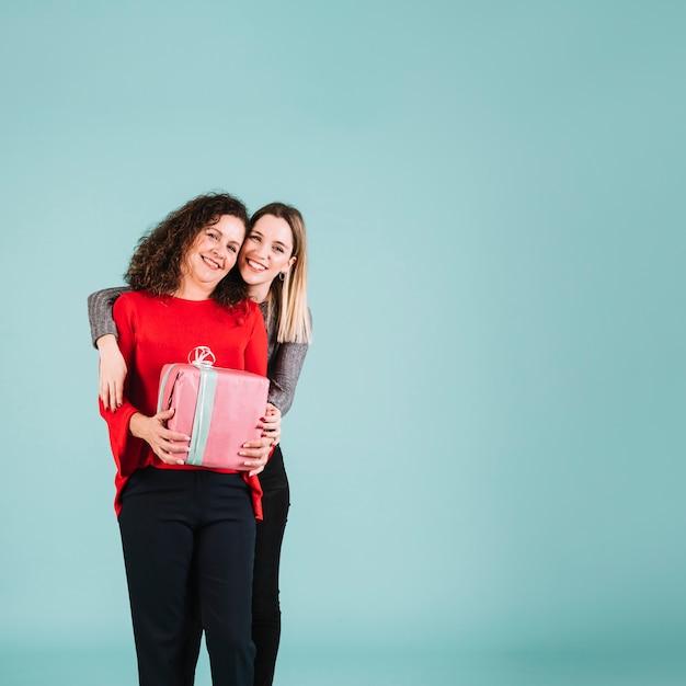 Figlia che abbraccia madre con regalo Foto Gratuite