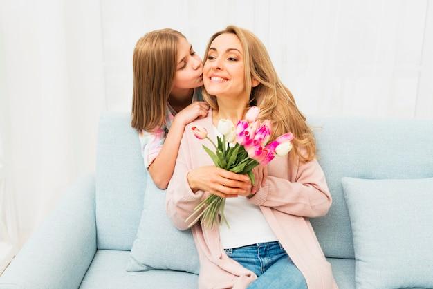 Figlia che bacia madre felice con i fiori Foto Gratuite