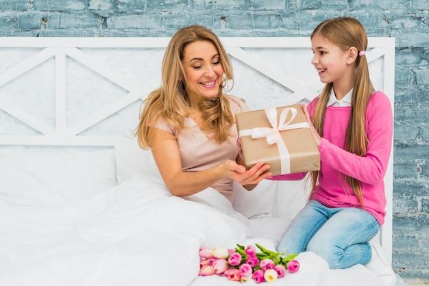 Figlia che dà il contenitore di regalo alla madre a letto Foto Gratuite