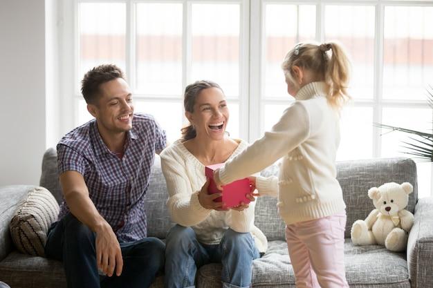 Figlia che dà il contenitore di regalo della mamma che presenta il giorno di madri Foto Gratuite
