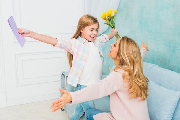 Figlia con doni di fiori e cartolina che abbraccia la madre Foto Gratuite