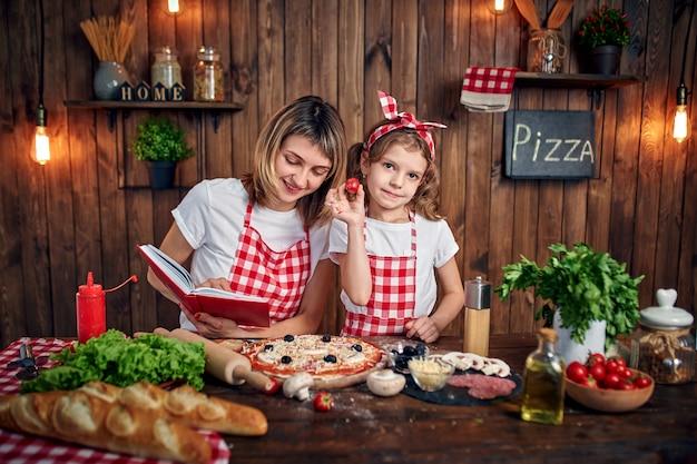 Figlia d'istruzione della madre che cucina pizza e sorridere Foto Premium