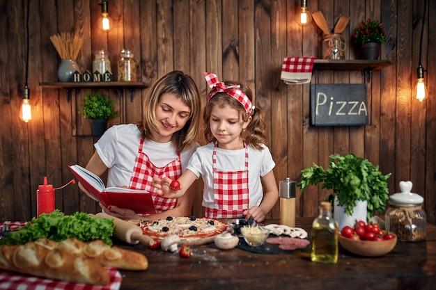 Figlia d'istruzione della madre che cucina pizza Foto Premium