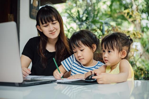 Figlia della scuola materna e della madre che per mezzo del computer portatile per lo studio a casa. Foto Premium