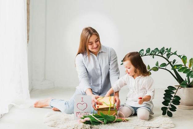 Figlia e madre che aprono la scatola regalo Foto Gratuite