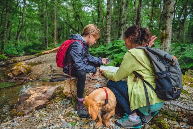 Figlia e madre escursioni nella foresta e usando la bussola Foto Premium