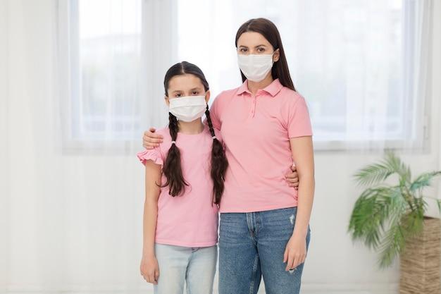 Figlia e ragazza che indossano maschere Foto Gratuite
