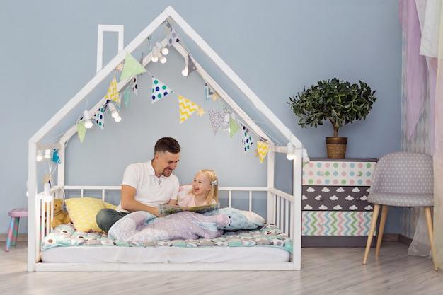 Figlia felice con suo padre bello che sorride mentre leggendo un libro nel letto sveglio della casa bianca Foto Premium