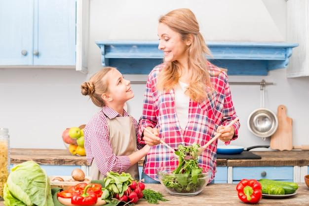 Figlia guardando sua madre mentre prepara l'insalata in cucina Foto Gratuite