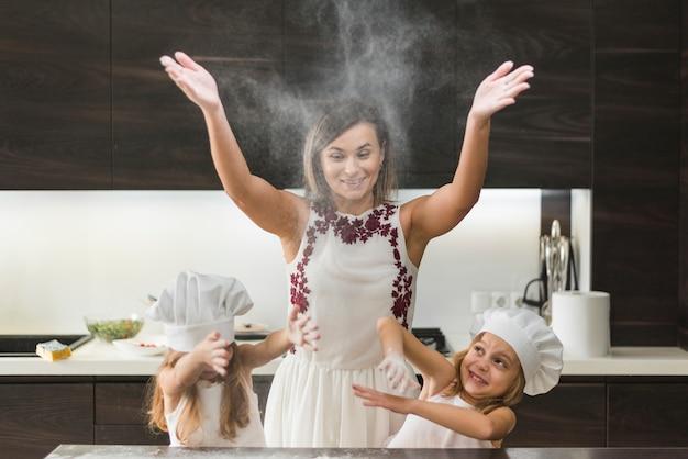 Figlie piccole con la madre che lancia la farina e divertirsi mentre si prepara il cibo Foto Gratuite