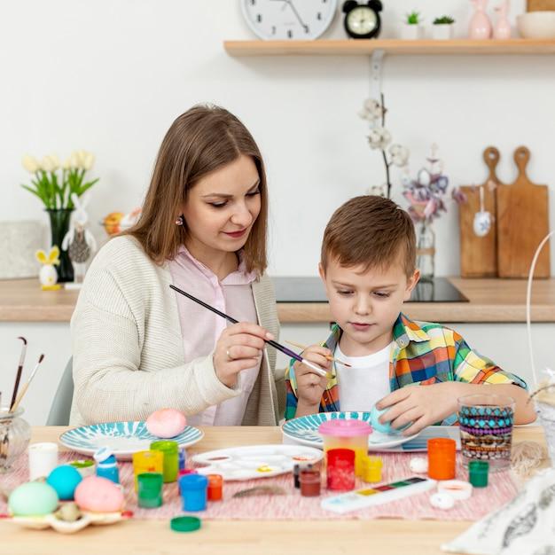 Figlio d'aiuto della mamma dell'angolo alto per dipingere le uova Foto Gratuite