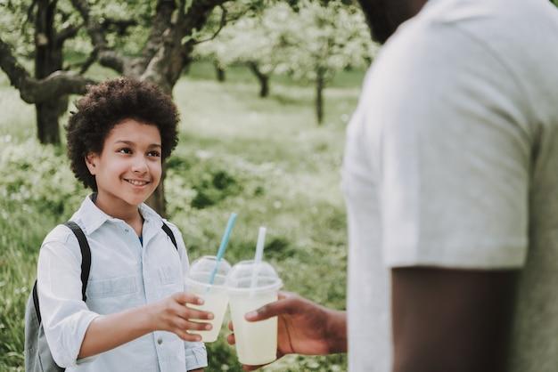 Figlio e padre salute e bere succo di frutta insieme. Foto Premium