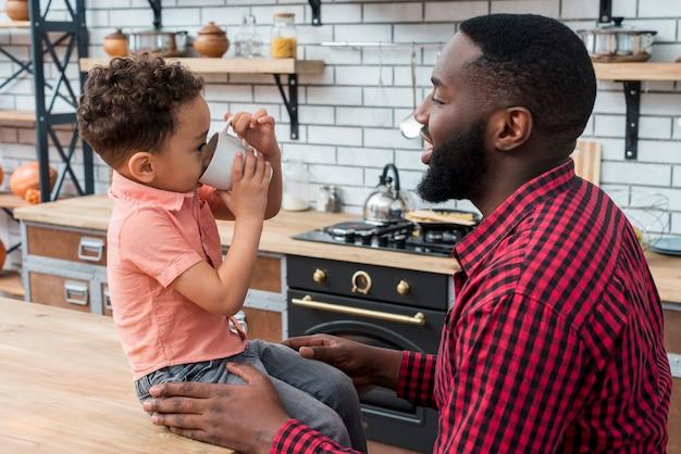 Figlio nero che beve tè con il padre Foto Gratuite