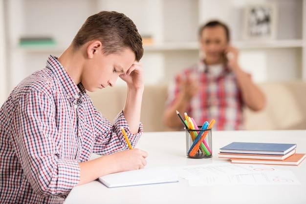 Figlio seduto alla scrivania mentre suo padre parla al telefono. Foto Premium