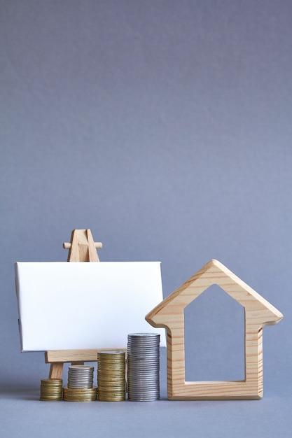 Figura di casa in legno con diverse colonne di monete nelle vicinanze e lavagna Foto Premium