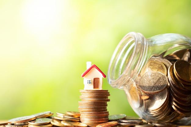 Figura di forma di casa rossa sulla pila e pila di monete Foto Premium