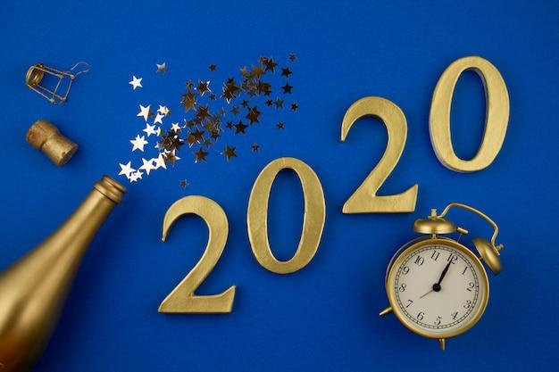 Figure di vista dall'alto, bottiglia d'oro di champagne, vetro, sveglia e confettie. festa, capodanno, celebrazione Foto Premium