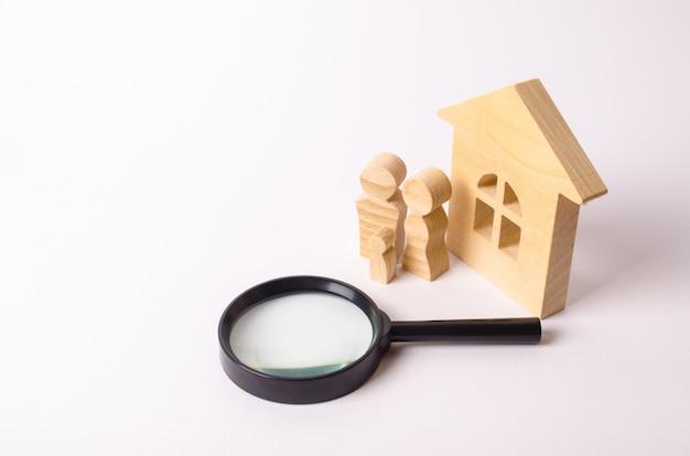 Figure in legno di persone sono in piedi vicino a una casa di legno e una lente d'ingrandimento. Foto Premium