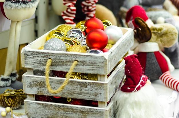 Figurine di giocattoli tradizionali per la decorazione domestica. scatola con sfere di vetro oro, argento, rosso sull'albero di natale per il nuovo anno. Foto Premium