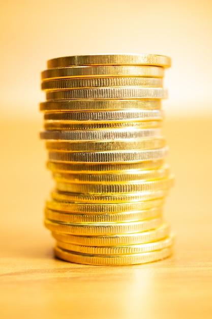 Fila delle monete sulla tavola di legno, immagine di vista frontale di orientamento verticale con il fuoco selettivo Foto Gratuite