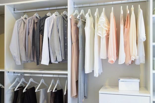 Fila di abito bianco e camicie appese nell'armadio bianco Foto Premium