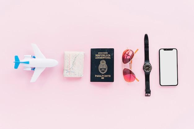 Fila di aeroplanino giocattolo; mappa piegata; passaporto; occhiali da sole; orologio da polso e smartphone su sfondo rosa Foto Gratuite