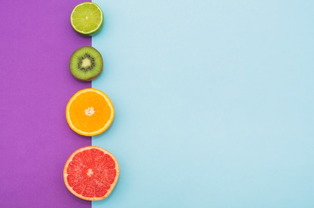 Fila di agrumi e kiwi divisi in due su doppio sfondo Foto Gratuite
