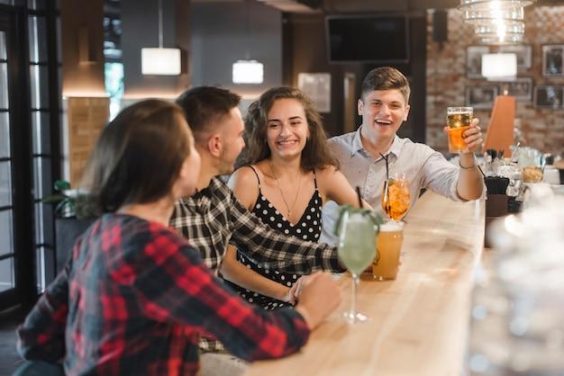Fila di amici che godono di drink al pub Foto Gratuite
