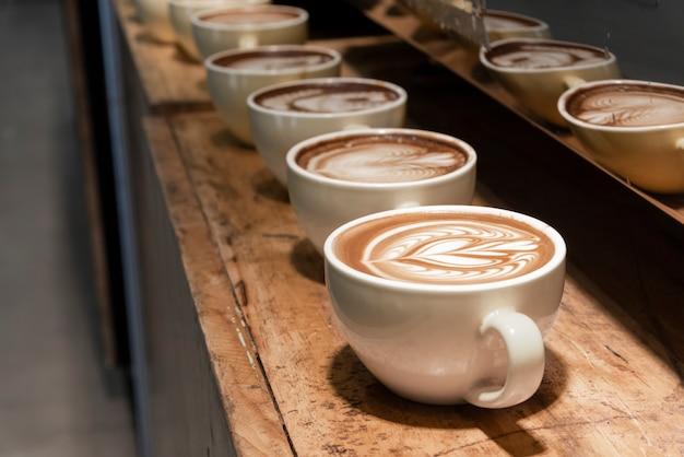 Fila di caffè latte art sullo scaffale in legno Foto Premium