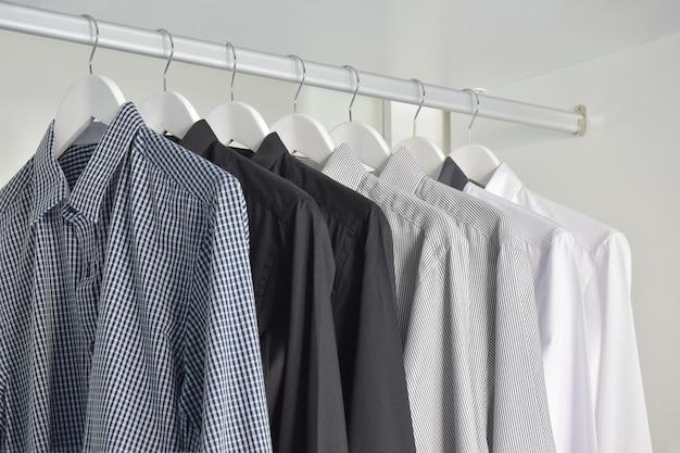 Fila di camicie bianche, grigie, nere appese nell'armadio di legno Foto Premium