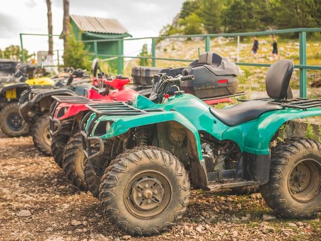 Fila di moto elettriche atv in un giorno d'estate in una zona di parcheggio di montagna Foto Premium