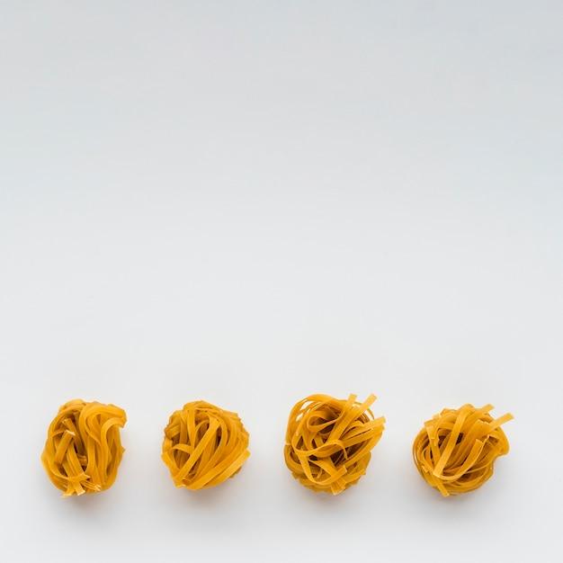 Fila di pasta cruda di tagliatelle sul fondo di fondo bianco Foto Gratuite
