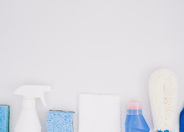 Fila di prodotti per la pulizia su sfondo bianco Foto Gratuite